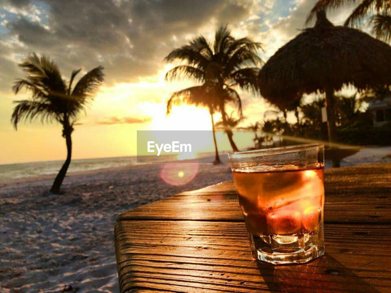 beach, palm tree, sunset, alcohol, sea, food and drink, drink, drinking glass, sky, sand, table, outdoors, vacations, cloud - sky, tropical climate, silhouette, summer, tree, water, travel destinations, no people, nature, day, close-up, tequila - drink, horizon over water, freshness