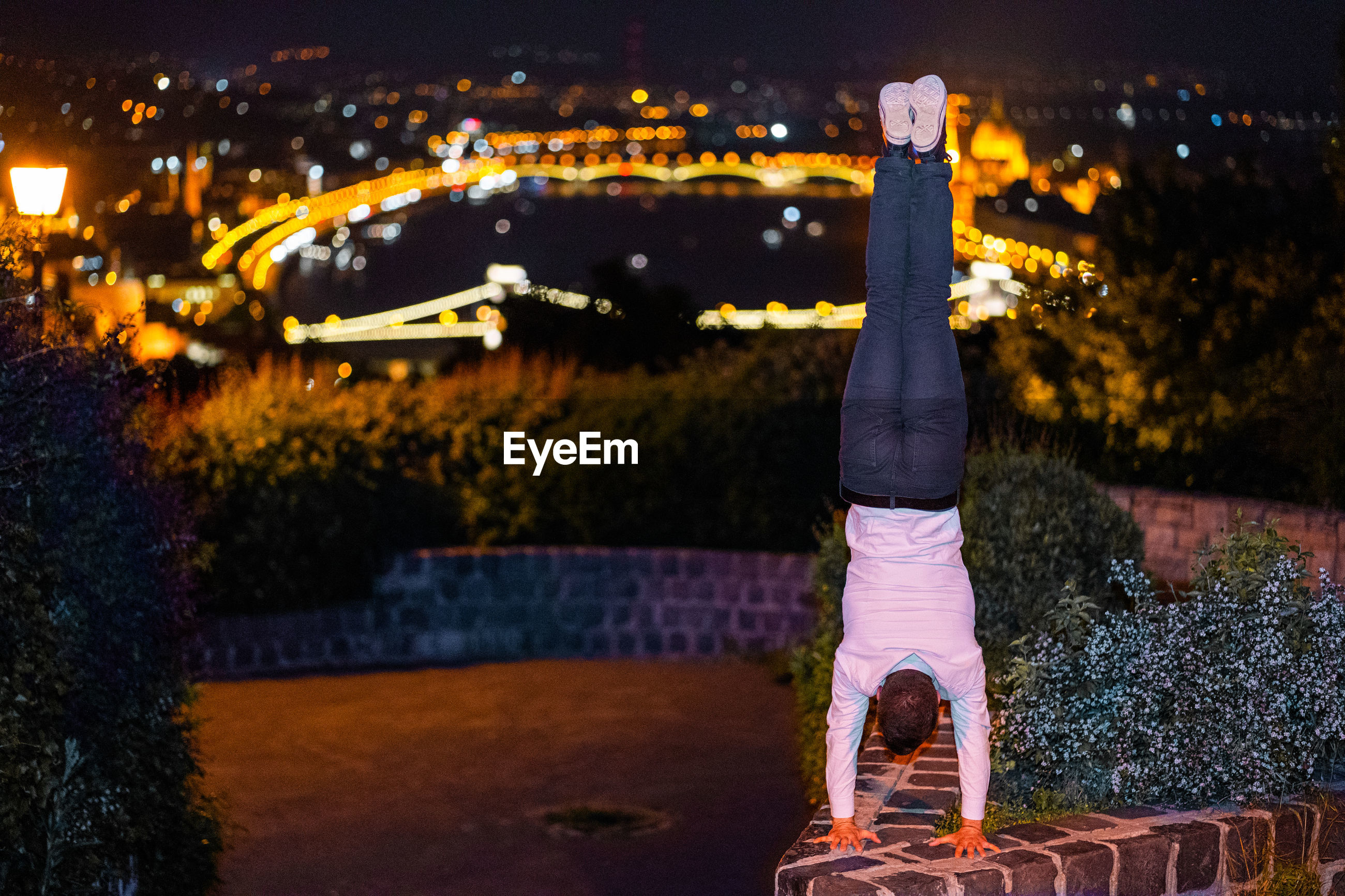Rear view of man doing handstand on retaining wall against illuminated city at night