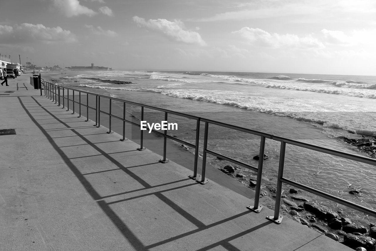 Shadow Of Metal Railing Against Sea At Carcavelos