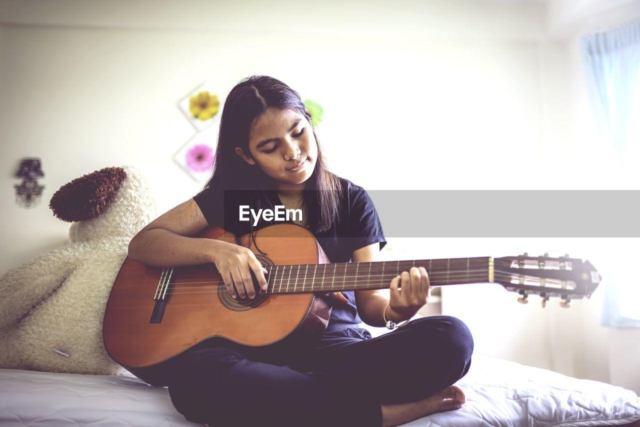 Teenage girl playing guitar on bed