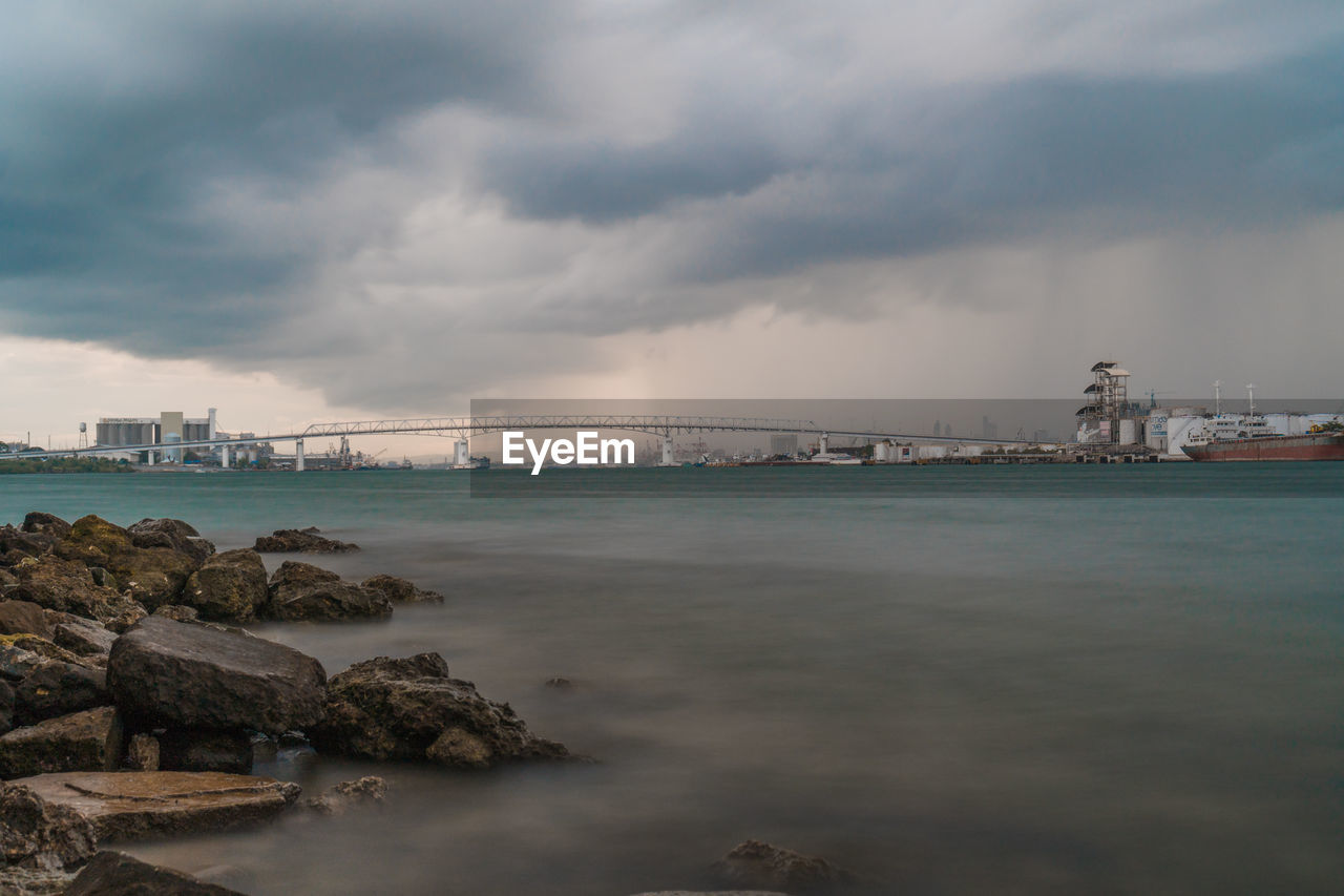 cloud - sky, sky, water, architecture, built structure, bridge, bridge - man made structure, connection, transportation, nature, no people, sea, building exterior, outdoors, city, waterfront, beauty in nature, bay