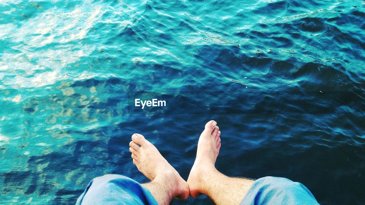 low section, barefoot, water, human leg, real people, personal perspective, one person, human foot, leisure activity, human body part, relaxation, lifestyles, day, sea, outdoors, men, rippled, blue, vacations, nature, close-up