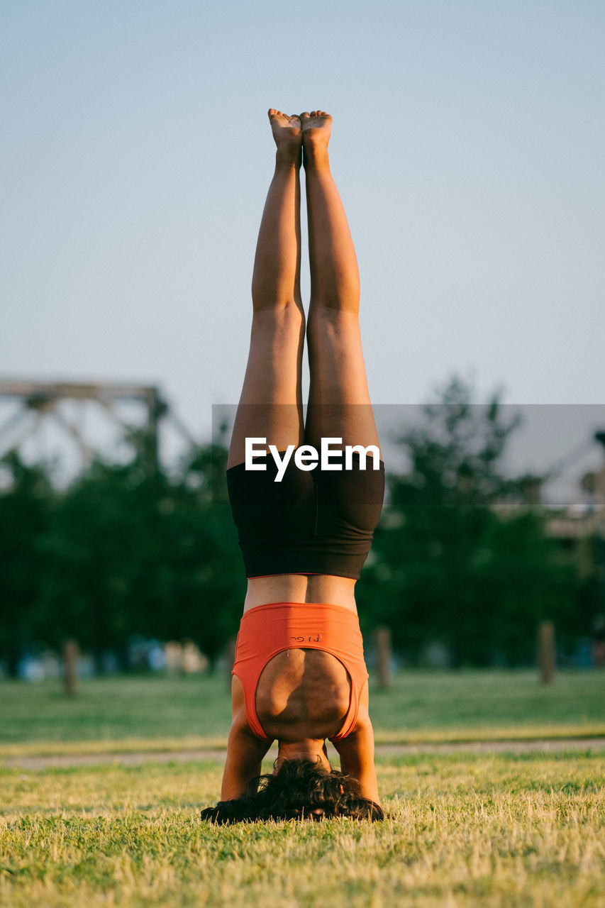 Upside down image of woman exercising on grassy field