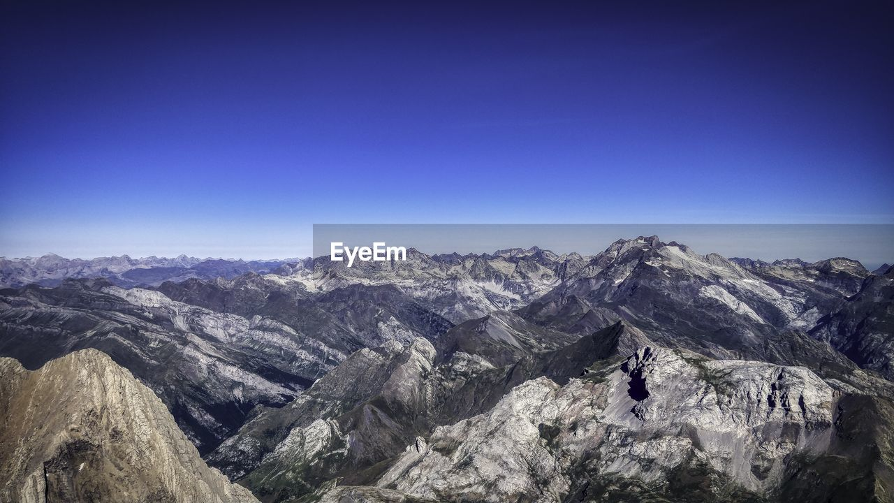 mountain, sky, beauty in nature, clear sky, rock, scenics - nature, tranquil scene, blue, tranquility, mountain range, nature, environment, landscape, copy space, mountain peak, non-urban scene, adventure, hiking, remote, day, outdoors, formation, high