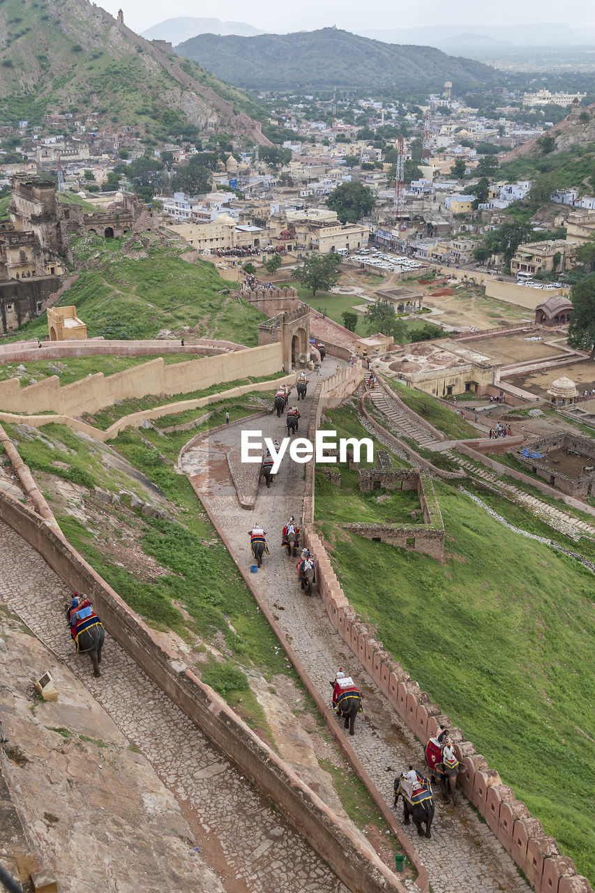 high angle view, architecture, history, group of people, real people, mountain, ancient, the past, built structure, day, incidental people, nature, tourism, travel destinations, adult, men, travel, people, old ruin, environment, outdoors, ancient civilization, archaeology, ruined