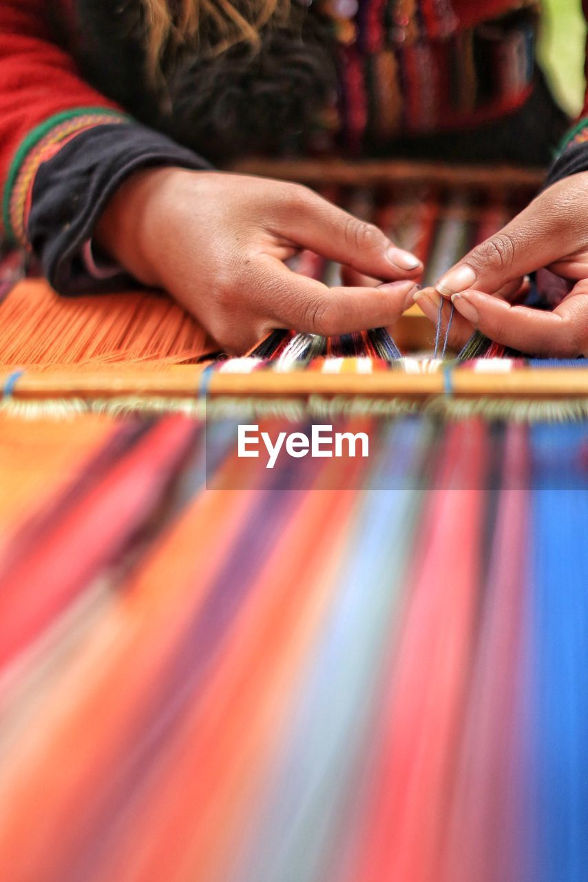 Midsection Of Person Weaving Loom
