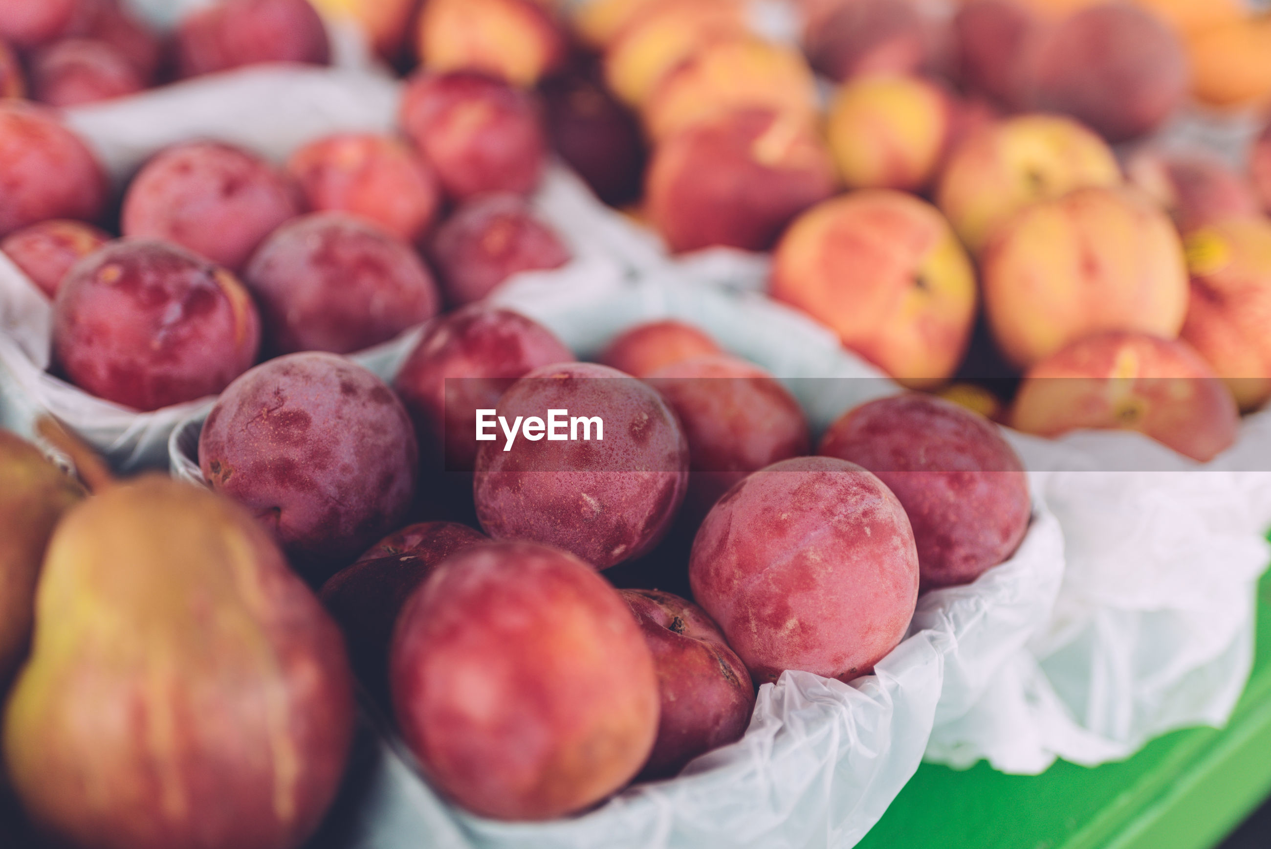 Close-up of plums for sale at market stall