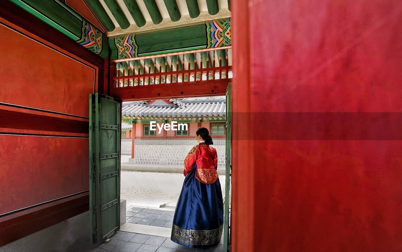 Rear view of woman standing in traditional clothing at doorway