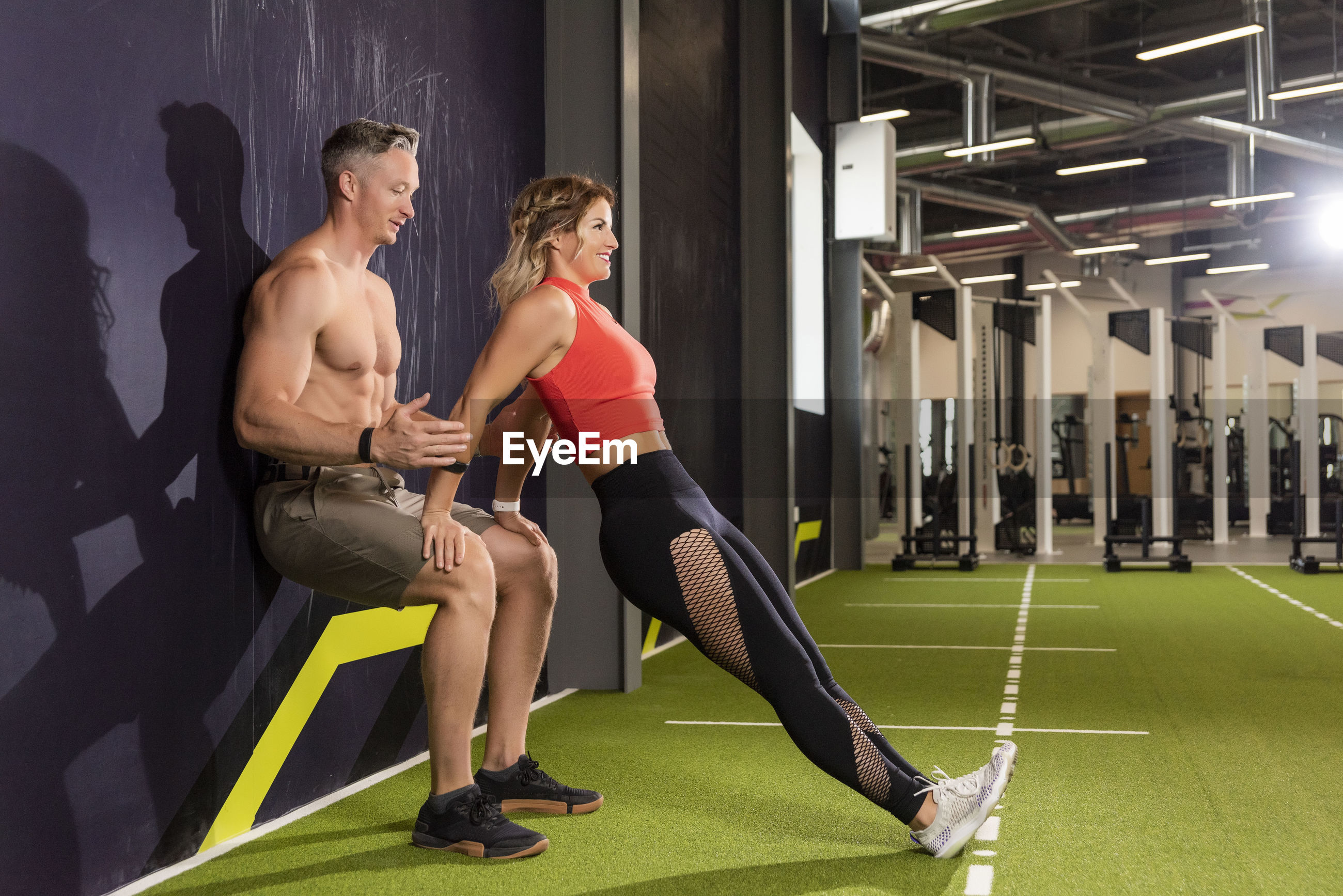 Male instructor assisting woman in exercising at gym