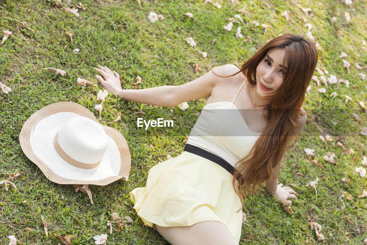 one person, grass, field, plant, young adult, lifestyles, nature, real people, young women, land, leisure activity, day, high angle view, casual clothing, women, smiling, long hair, looking at camera, hairstyle, beautiful woman, outdoors