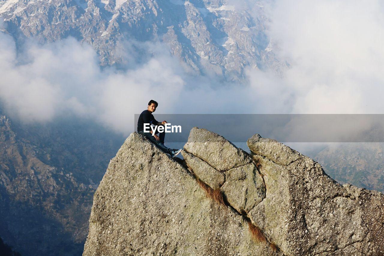 Full Length Of Man Sitting On Mountain At Mcleod Ganj
