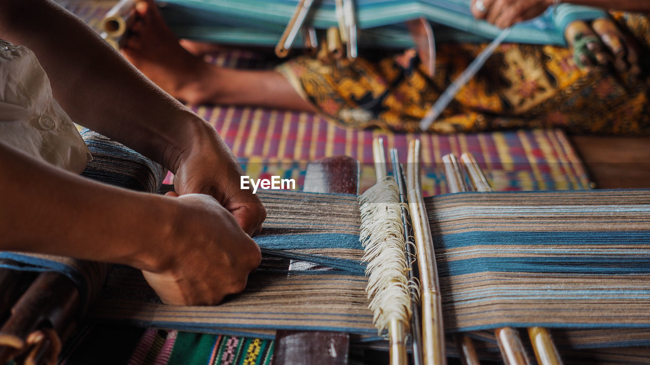 Cropped Hands Weaving With Loom In Factory