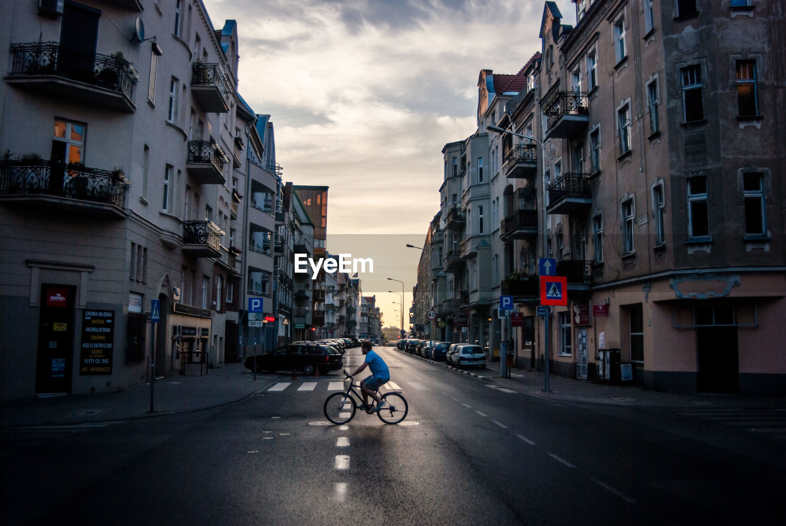 Side view of man riding bicycle on road in city