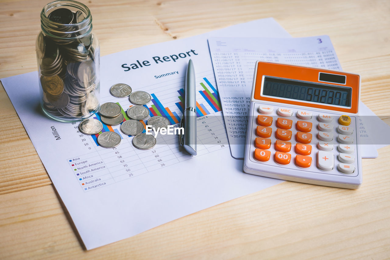 High angle view of coins with calculator and chart on table