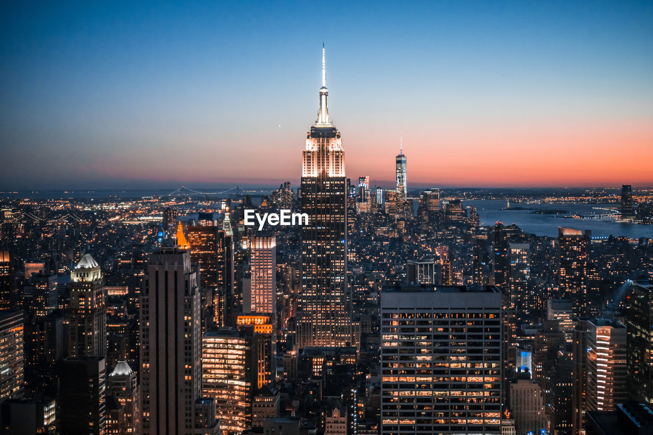 High Angle View Of Illuminated Empire State Building And City Against Clear Blue Sky At Night