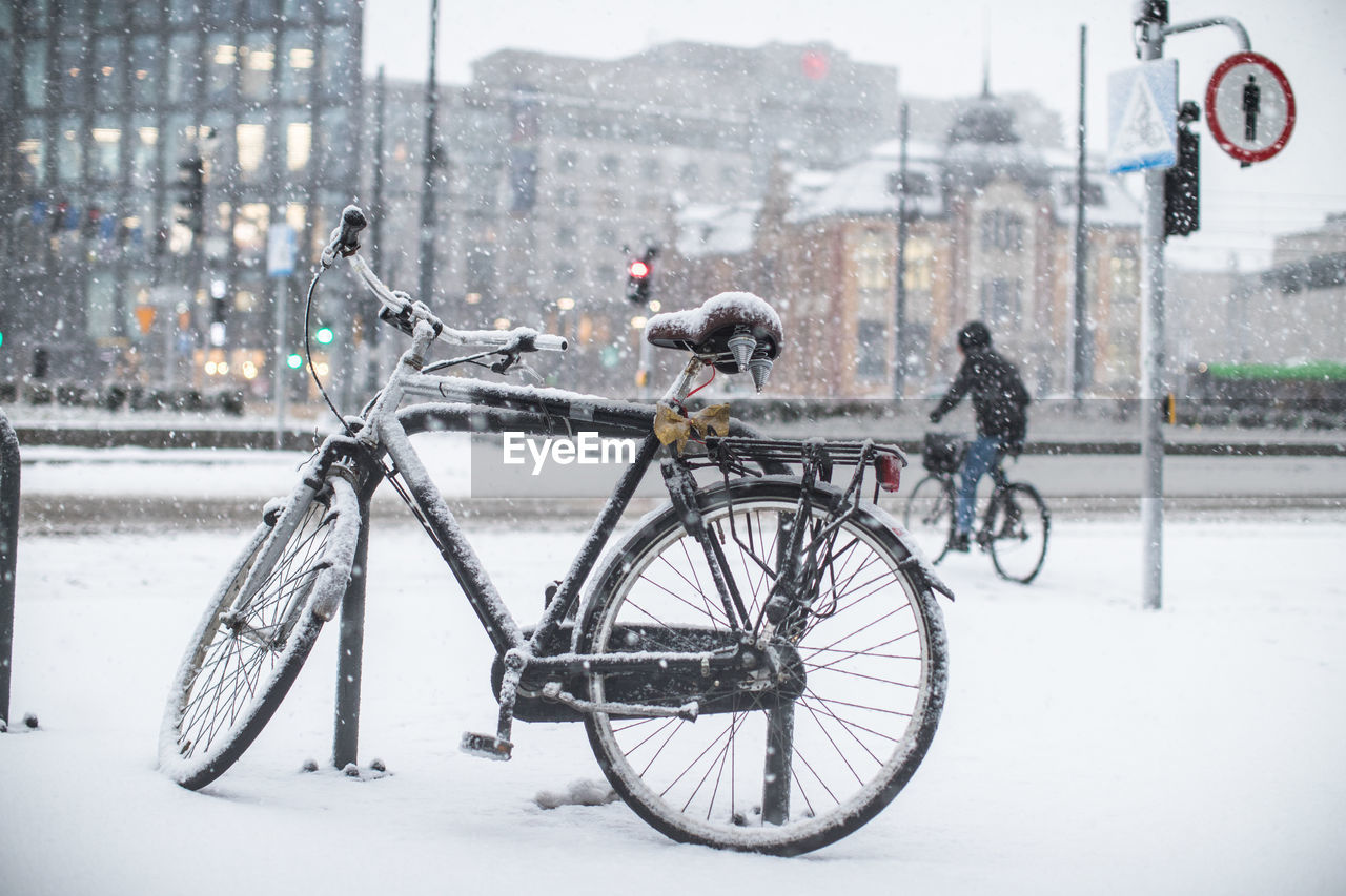 Bicycle on snow covered field in city