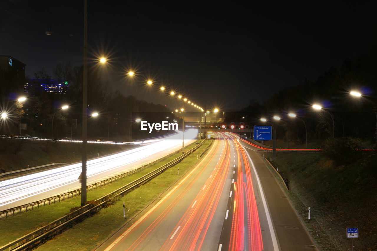 illuminated, night, transportation, street, street light, road, light trail, motion, speed, long exposure, lighting equipment, no people, city, the way forward, direction, sign, nature, architecture, highway, blurred motion, outdoors, multiple lane highway