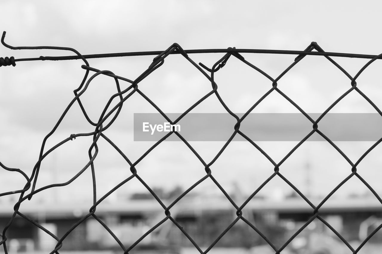 fence, barrier, boundary, protection, security, metal, safety, chainlink fence, sky, pattern, no people, focus on foreground, day, nature, close-up, outdoors, low angle view, forbidden, cloud - sky, wire