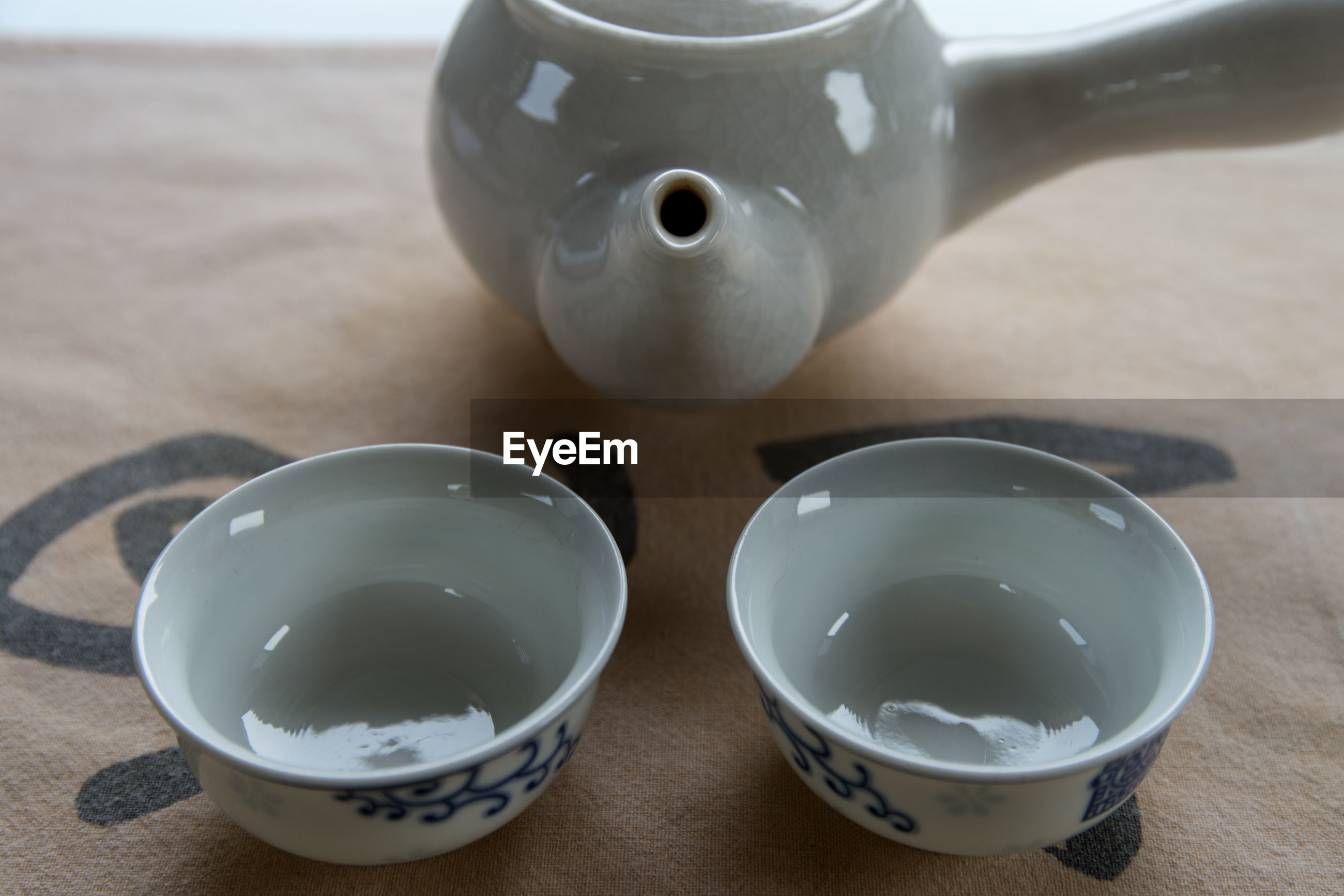 Close-up of tea cups and teapot on table