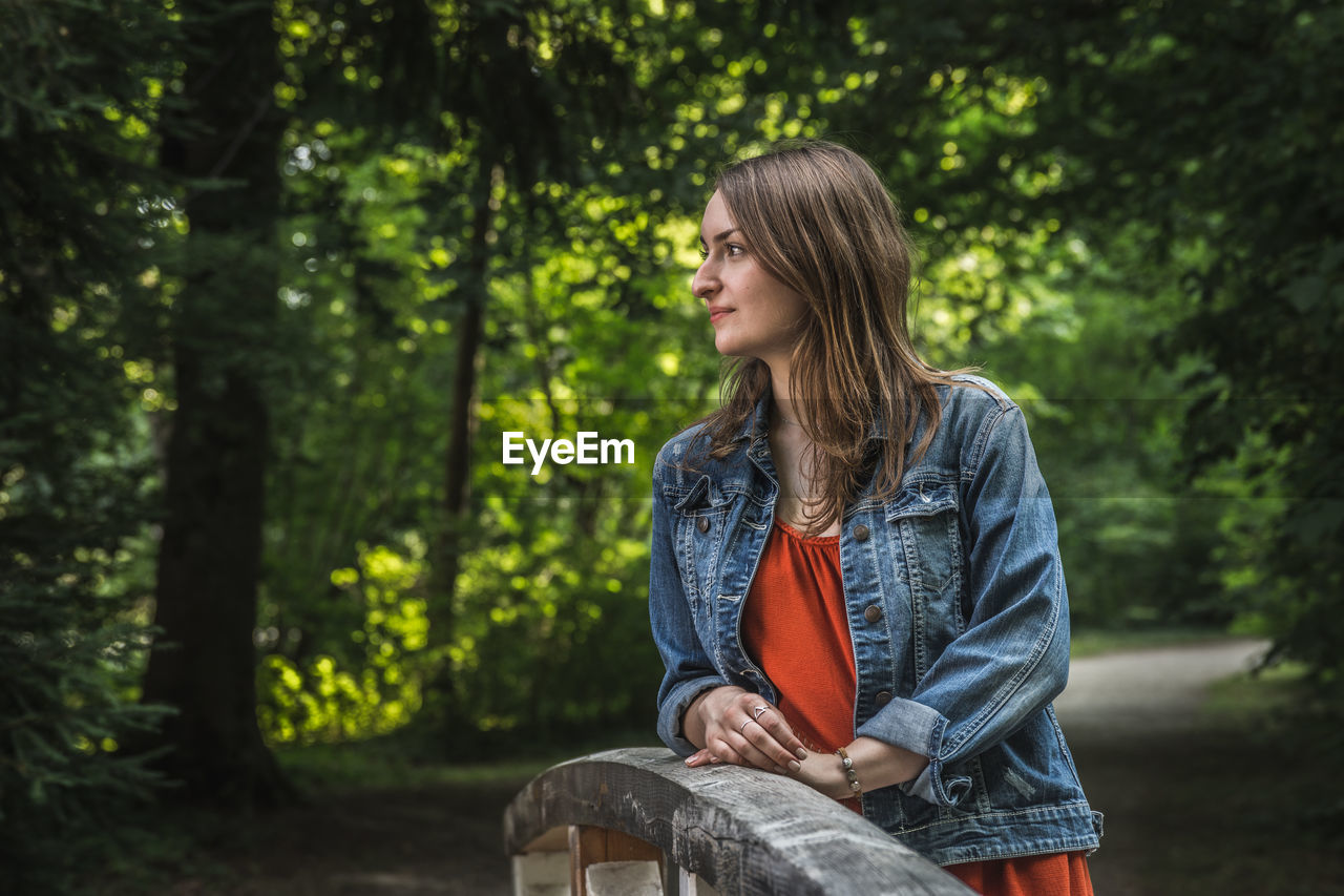 tree, one person, plant, leisure activity, casual clothing, real people, sitting, young adult, lifestyles, long hair, hairstyle, hair, forest, focus on foreground, land, young women, day, looking away, outdoors, beautiful woman, contemplation, teenager