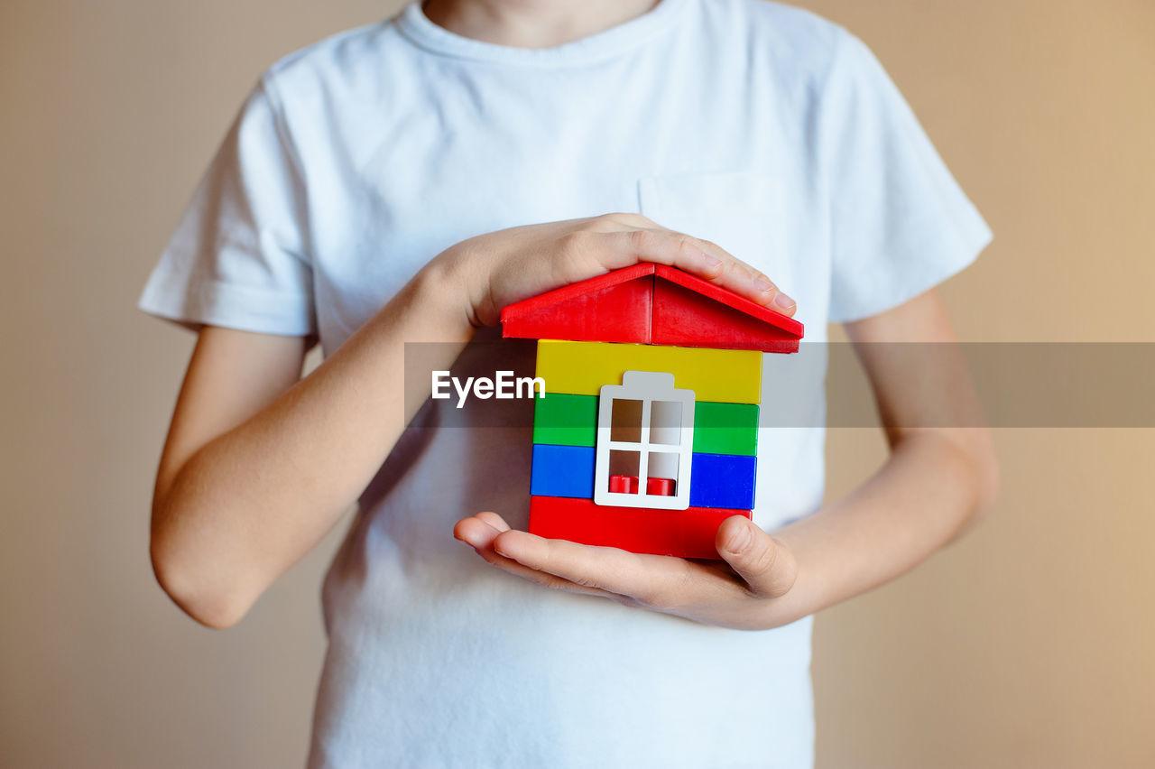 Boy Holding Toy House