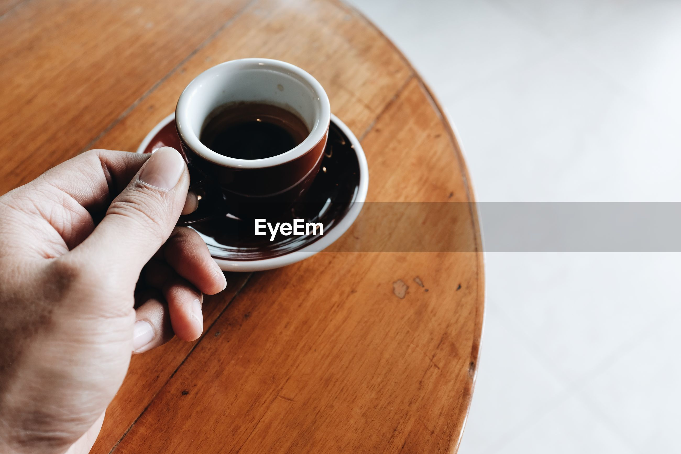 HIGH ANGLE VIEW OF HAND HOLDING COFFEE CUP ON WOODEN TABLE