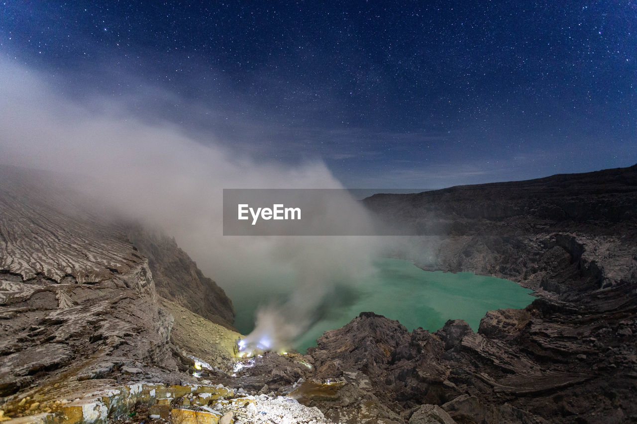 Smoke emitting from volcanic mountain against sky at night
