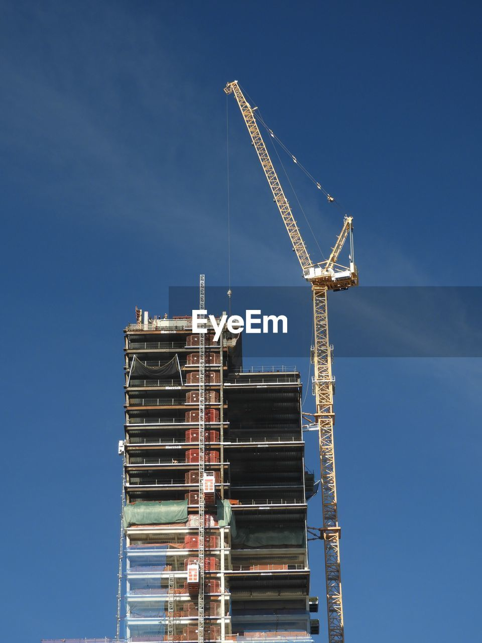 Low Angle View Of Crane At Under Construction Building Against Blue Sky