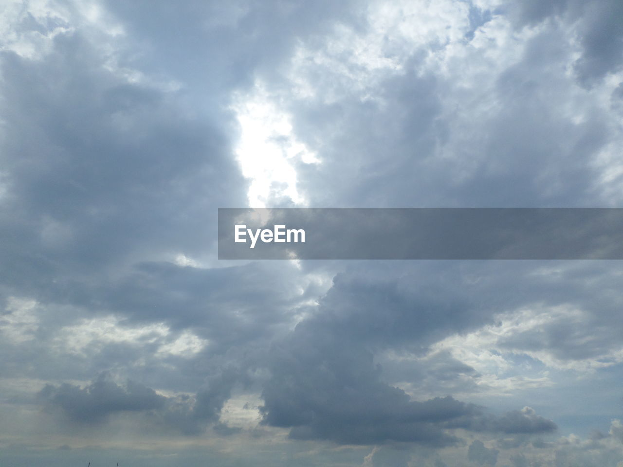 LOW ANGLE VIEW OF SUNLIGHT STREAMING THROUGH CLOUDS IN SKY