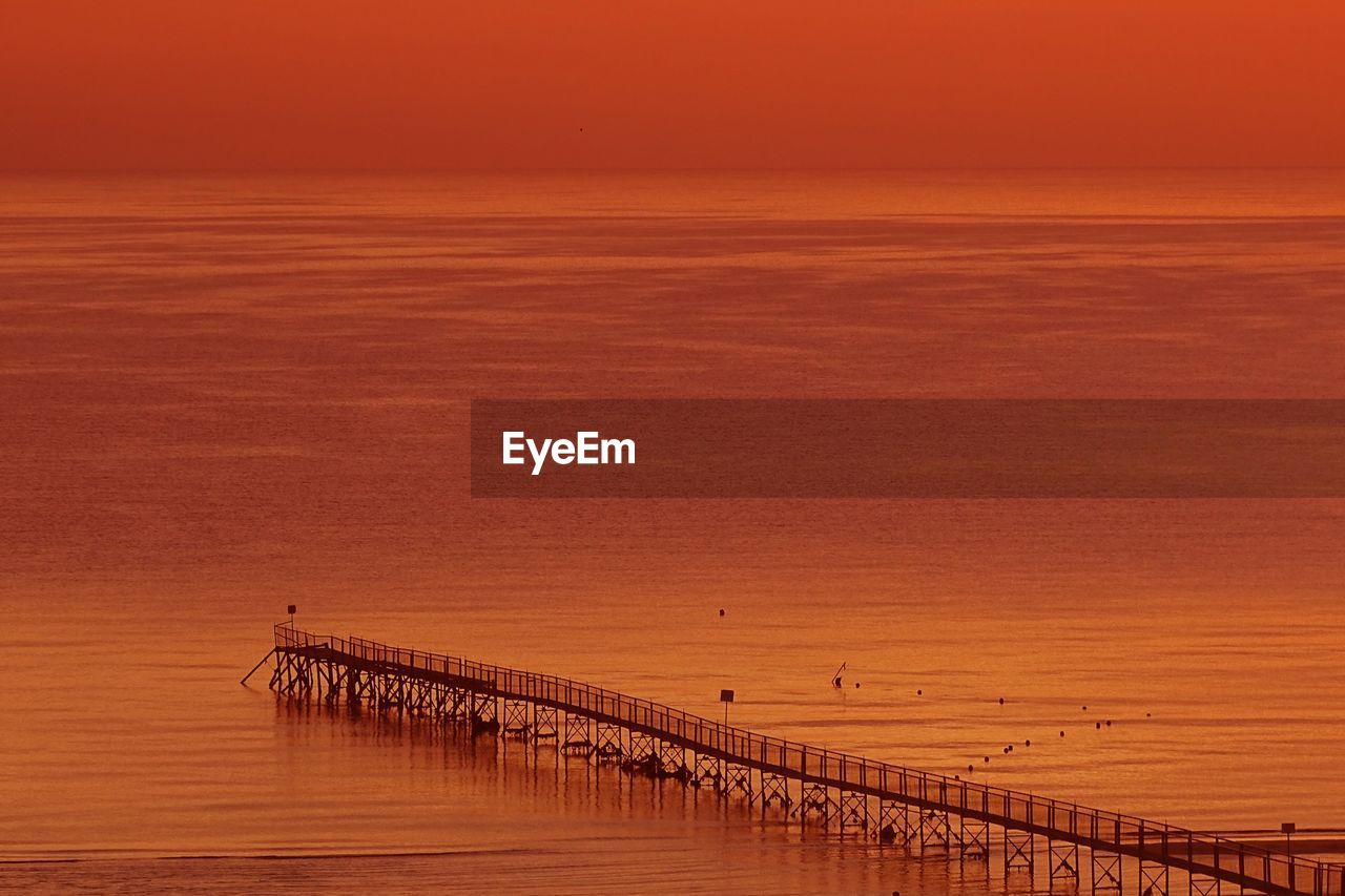 sky, water, scenics - nature, sunset, sea, beauty in nature, orange color, tranquility, tranquil scene, horizon, nature, horizon over water, waterfront, no people, pier, non-urban scene, outdoors, idyllic, wood - material