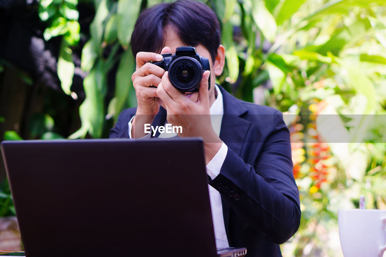 Businessman photographing with camera by laptop against trees