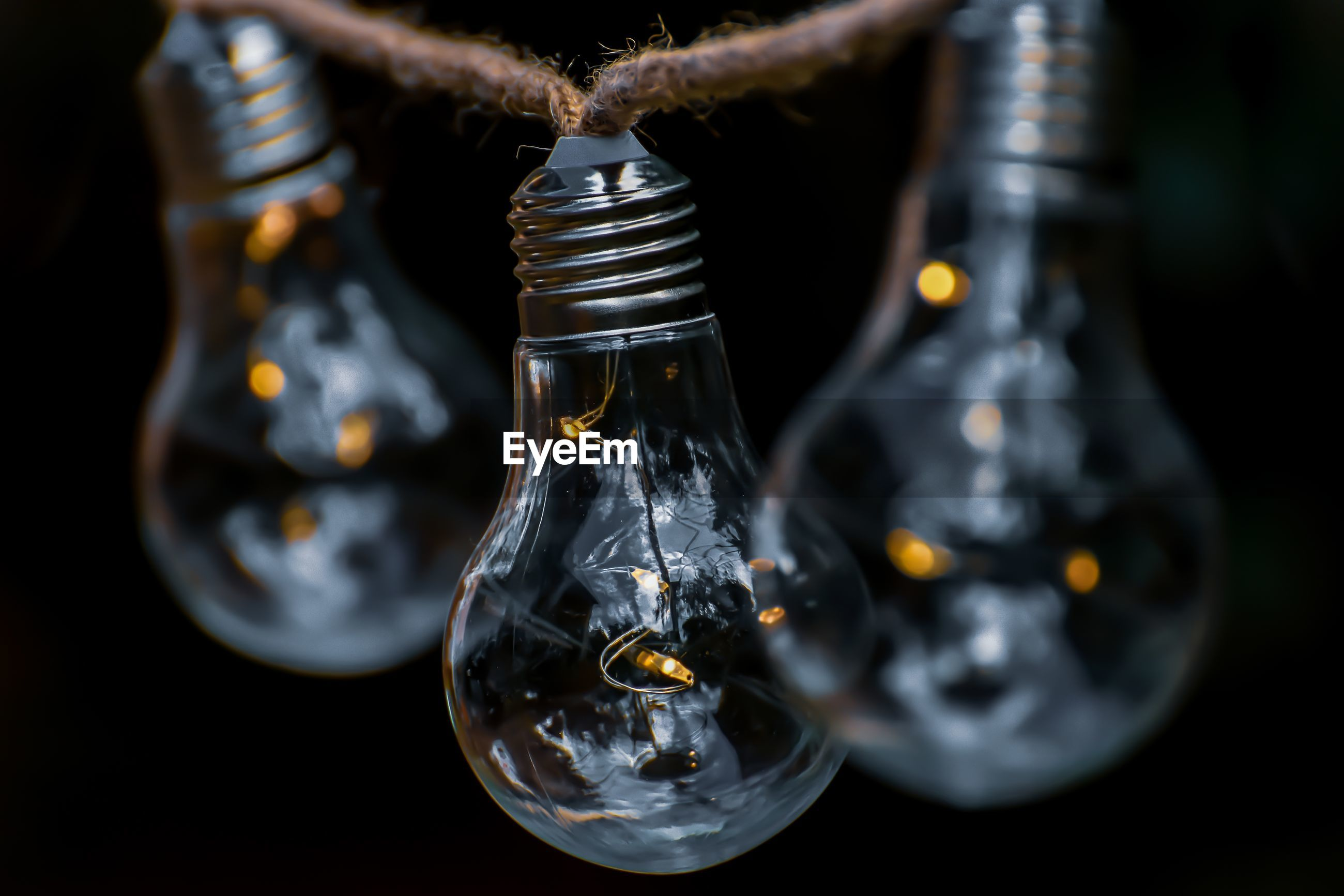 Close-up of light bulb hanging on rope outdoors