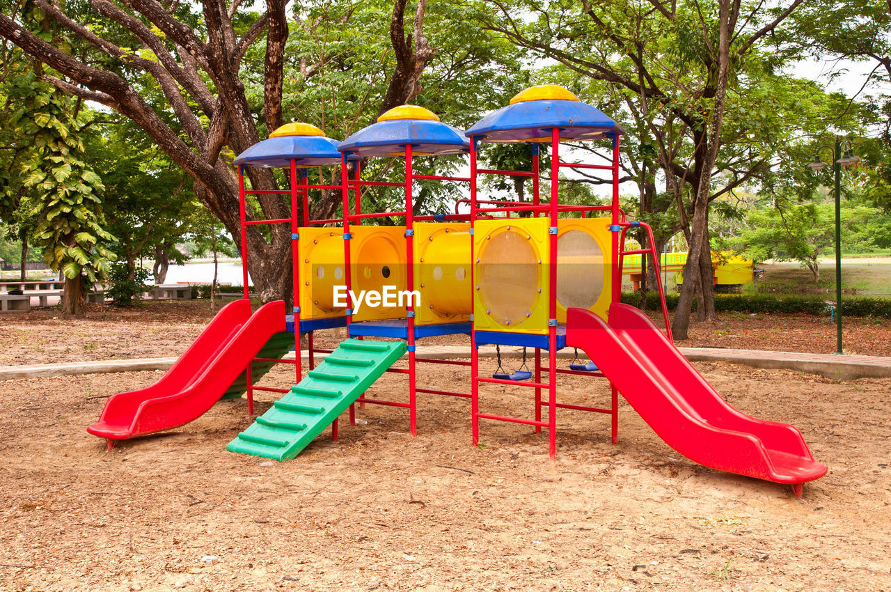playground, outdoor play equipment, park - man made space, childhood, tree, slide, absence, fun, day, multi colored, arts culture and entertainment, no people, outdoors, merry-go-round, water slide
