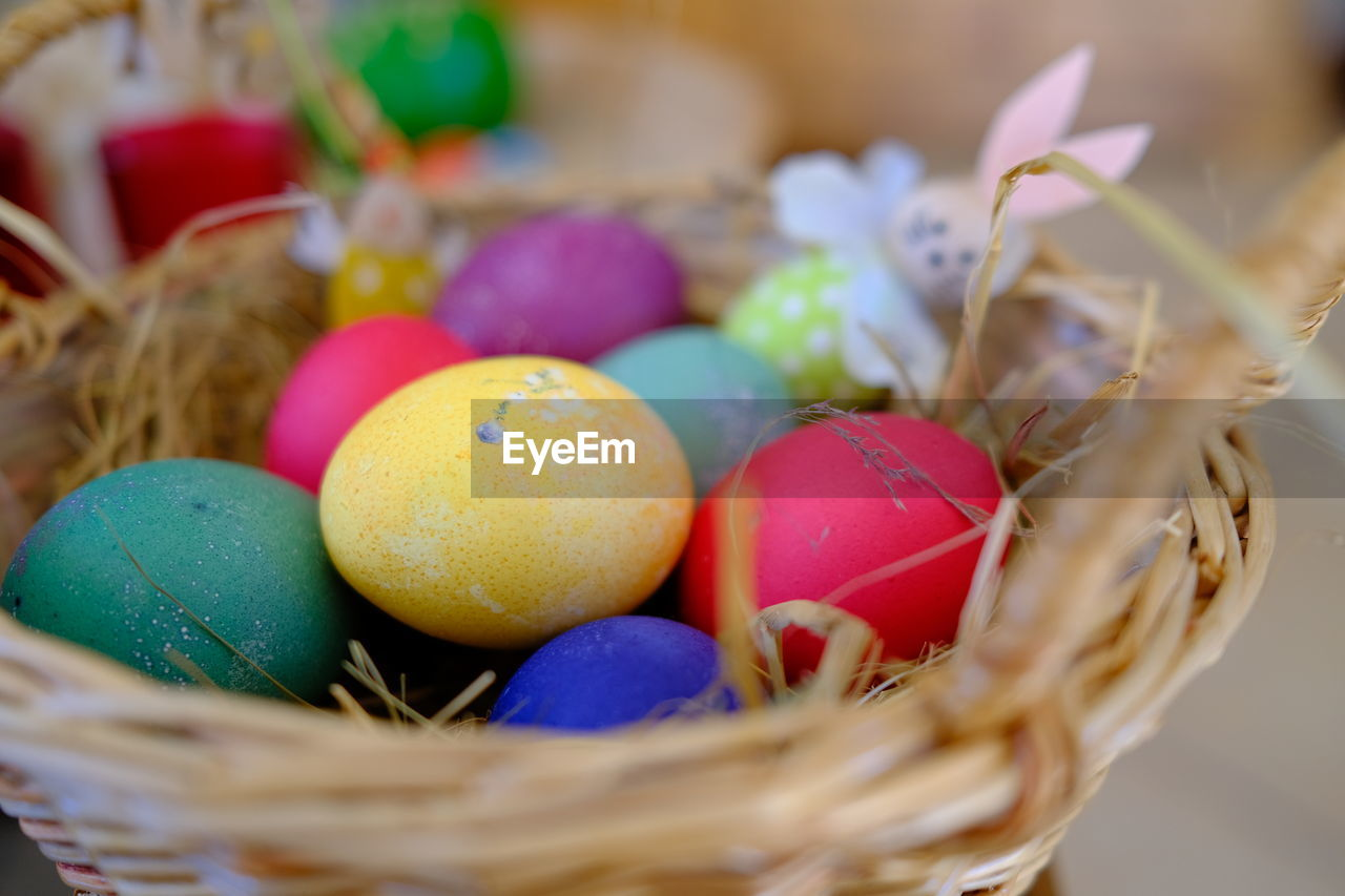 CLOSE-UP OF COLORFUL EGGS IN BASKET