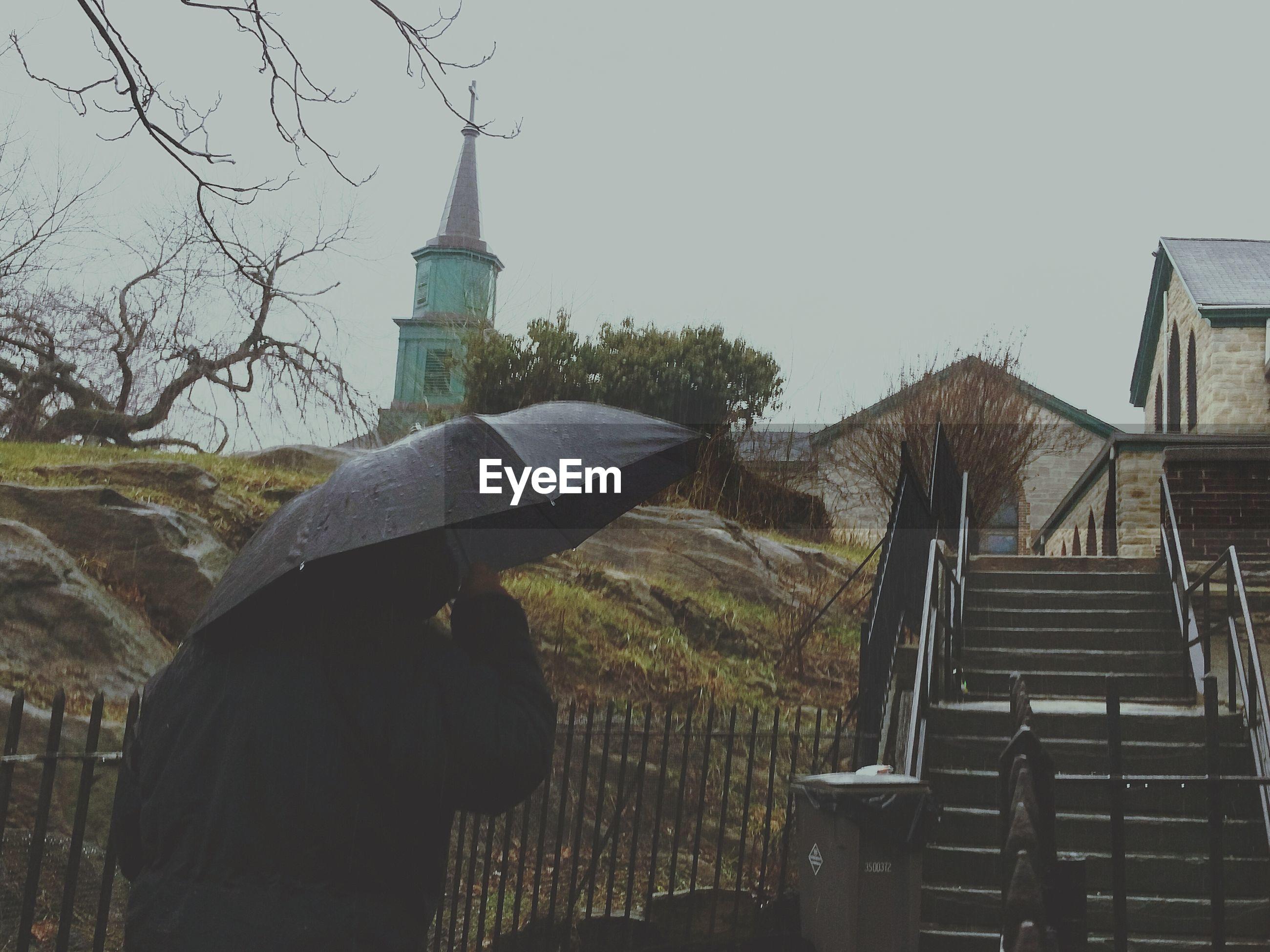 Rear view of man holding umbrella at st ann church