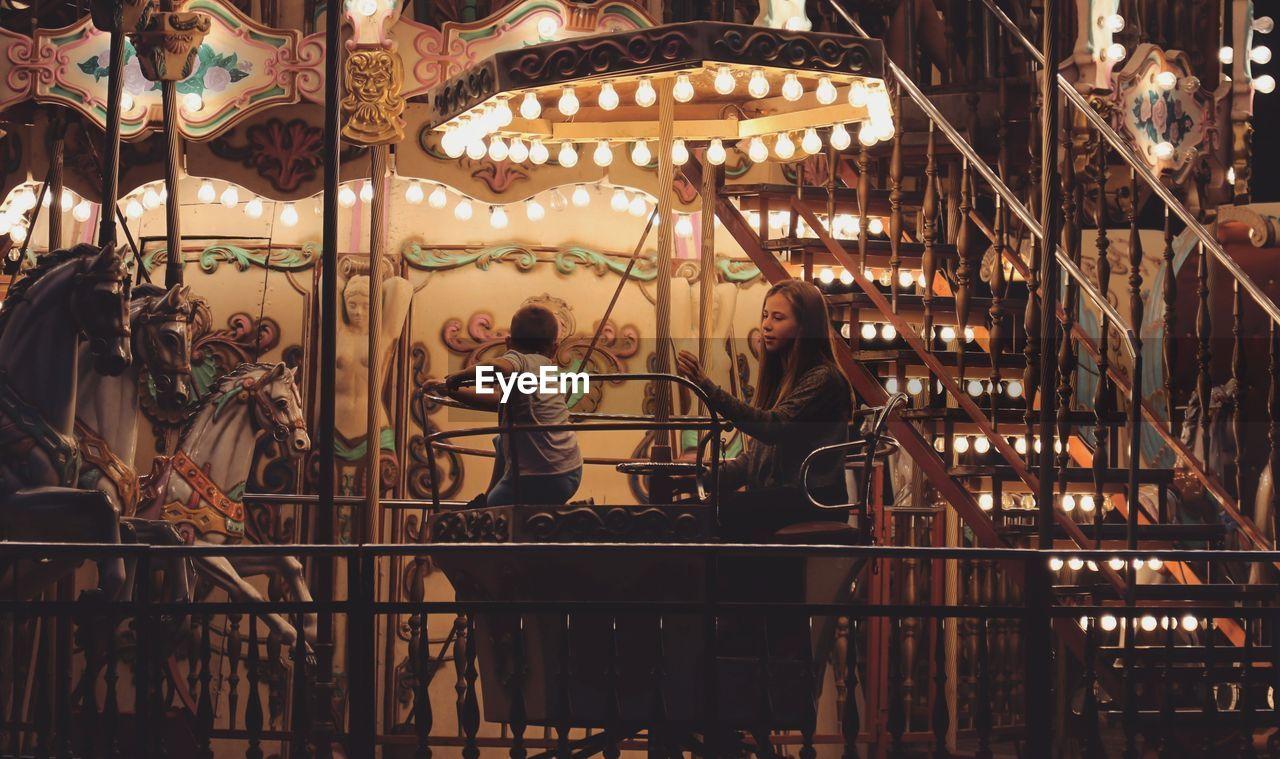 Siblings Sitting In Illuminated Carousel Horses At Night