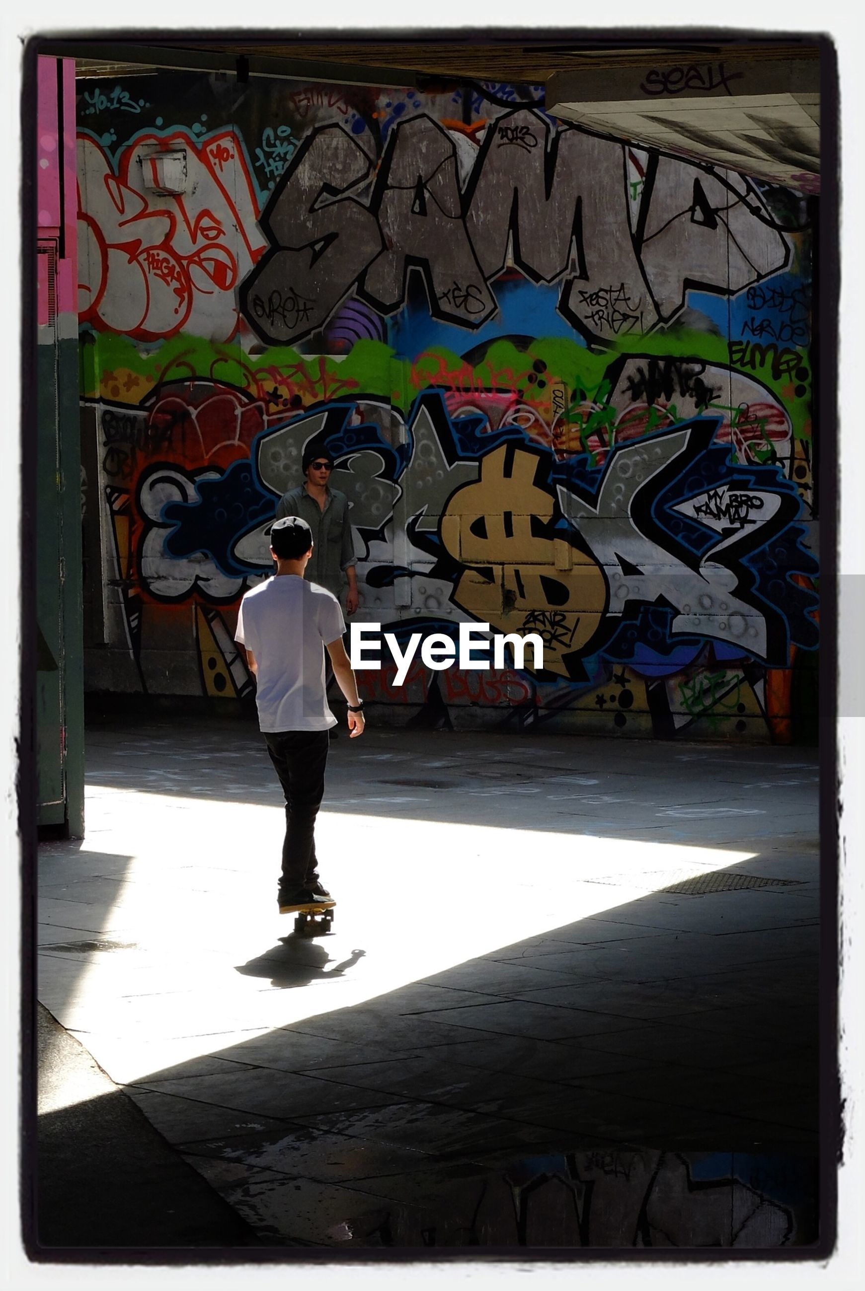 graffiti, architecture, built structure, full length, wall - building feature, lifestyles, art, art and craft, transfer print, creativity, standing, auto post production filter, leisure activity, building exterior, walking, wall, casual clothing, rear view