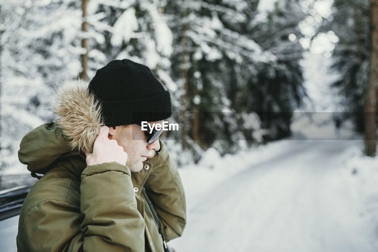 Man Wearing Fur Hood On Snow Covered Landscape