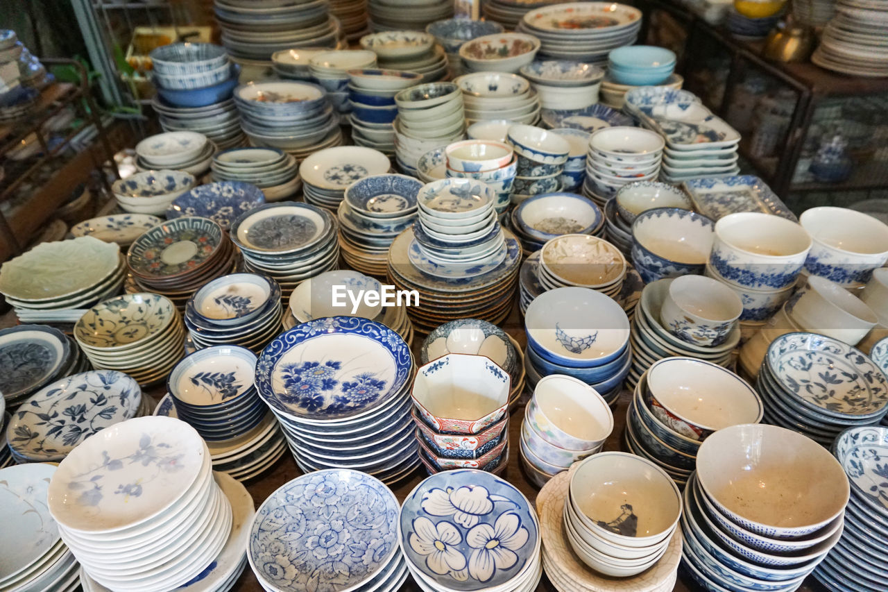 large group of objects, arrangement, abundance, for sale, choice, retail, high angle view, variation, stack, market, no people, ceramics, still life, indoors, market stall, full frame, in a row, container, order, pattern, retail display, antique, crockery