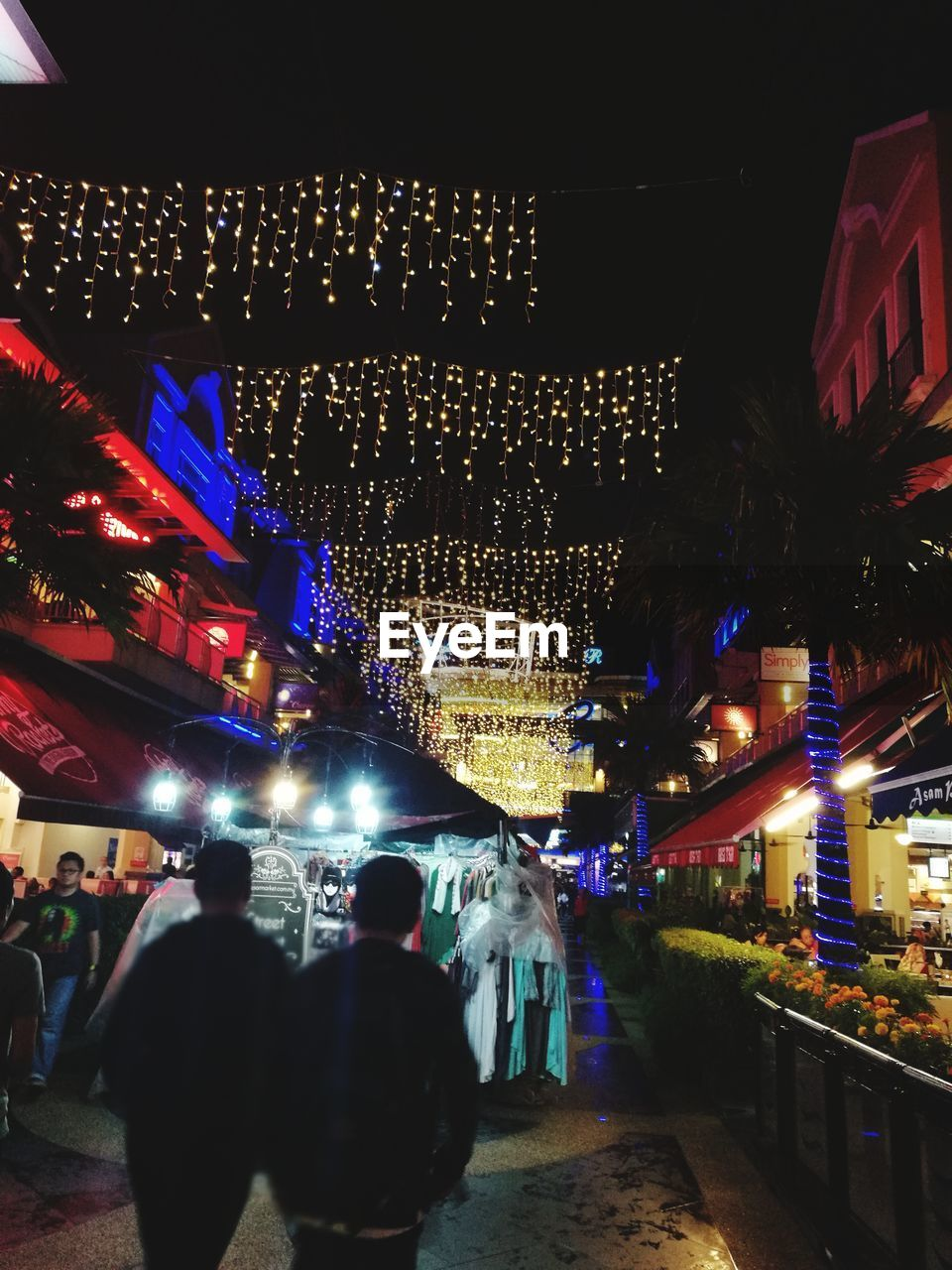 night, illuminated, built structure, building exterior, architecture, lighting equipment, large group of people, celebration, men, real people, christmas lights, women, rear view, lifestyles, christmas decoration, nightlife, leisure activity, crowd, city, outdoors, vacations, tree, sky, adult, people