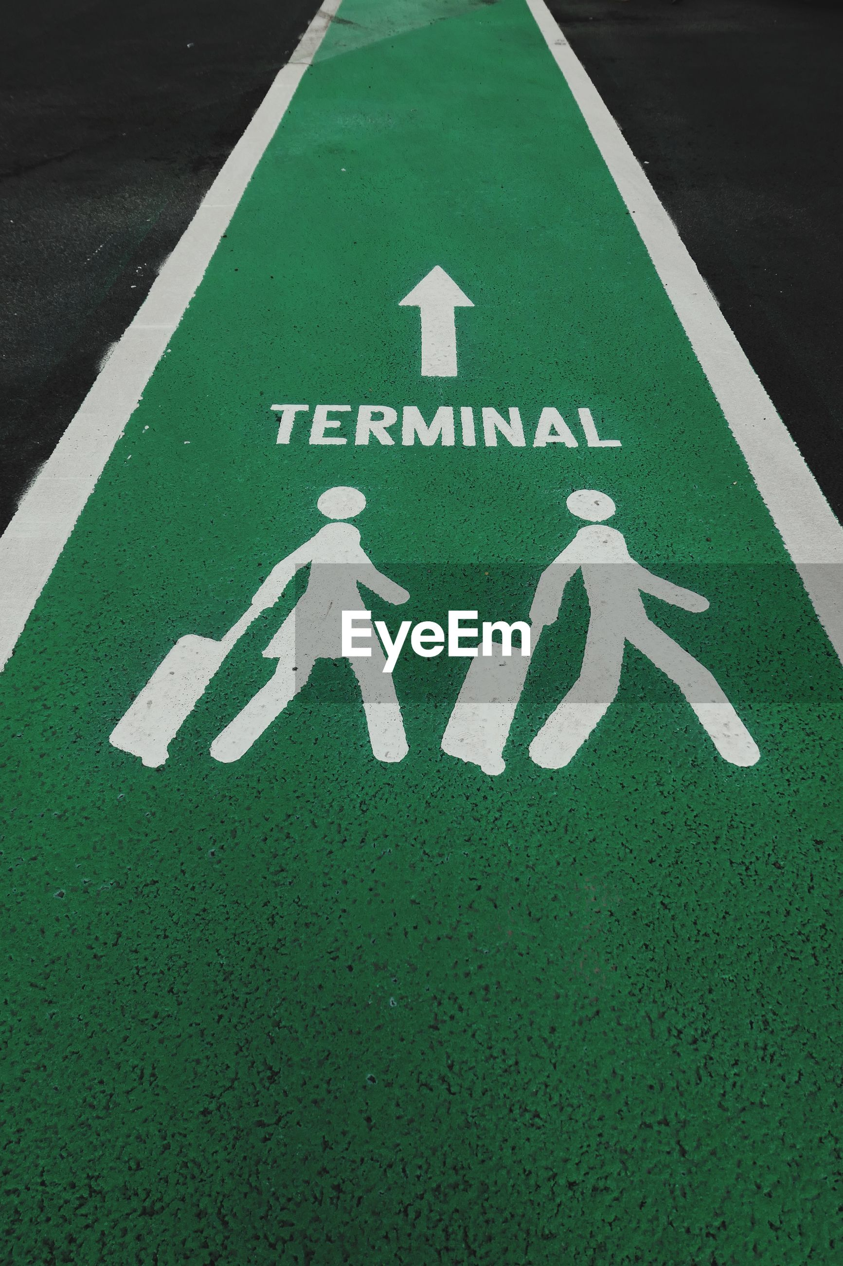 High angle view of text with human representation and arrow symbol on pathway at airport