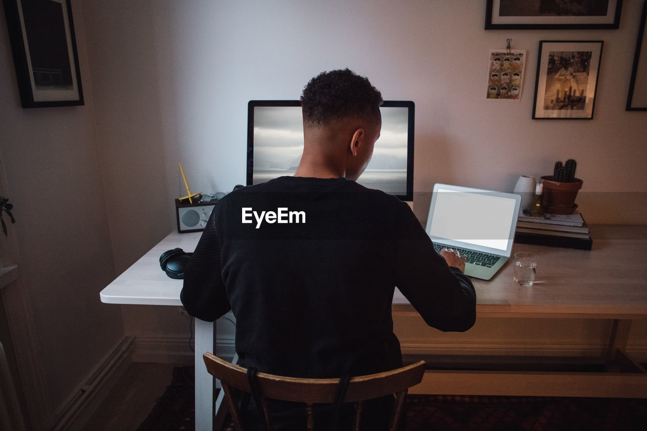 REAR VIEW OF MAN USING LAPTOP AT HOME