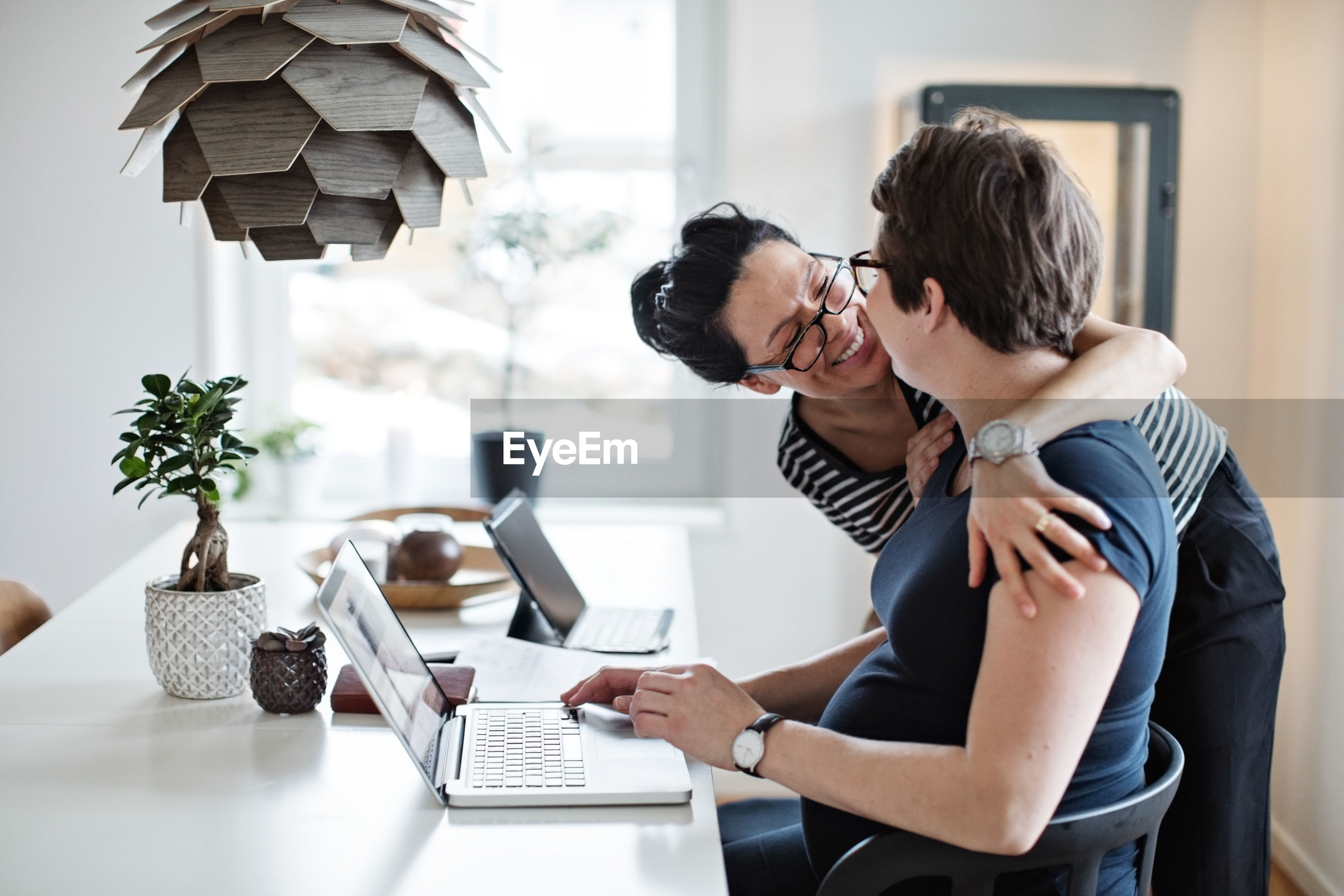 Smiling woman embracing girlfriend using laptop at table
