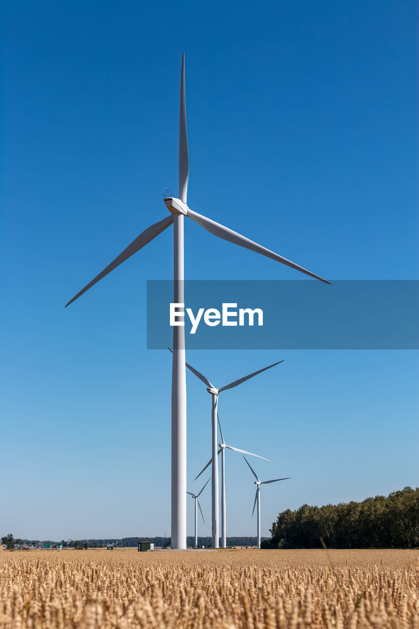 Windmills on scenic agricultural field against clear blue sky