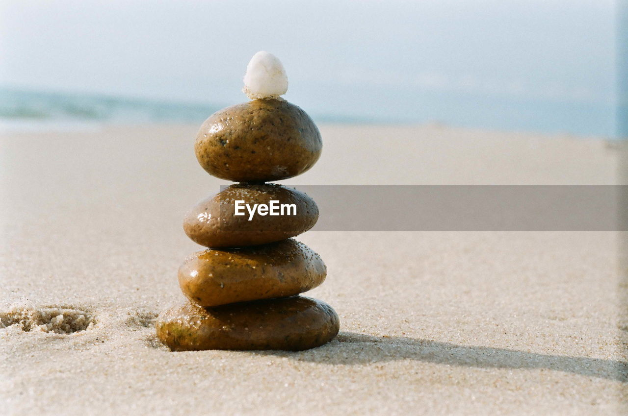 beach, stone - object, land, sea, balance, stack, zen-like, pebble, no people, sand, rock, solid, stone, nature, close-up, day, focus on foreground, water, still life, sunlight, outdoors