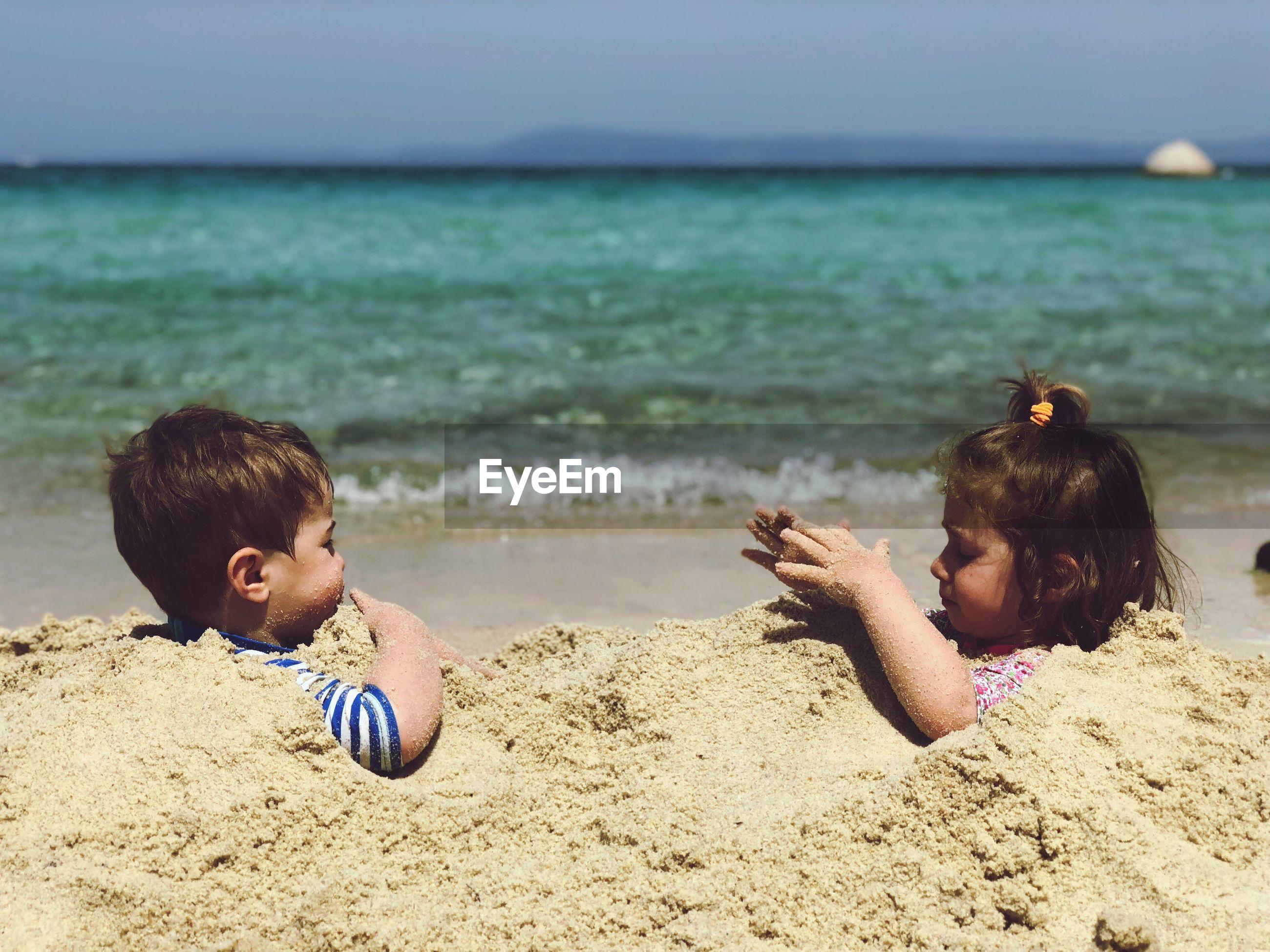 Playful children in sand at beach during summer