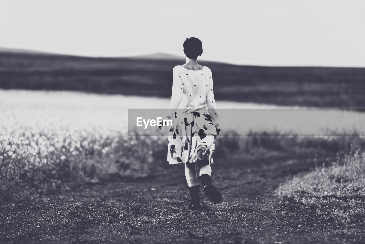 rear view, land, full length, one person, sky, field, standing, nature, real people, leisure activity, lifestyles, walking, women, grass, day, casual clothing, plant, men, adult, outdoors