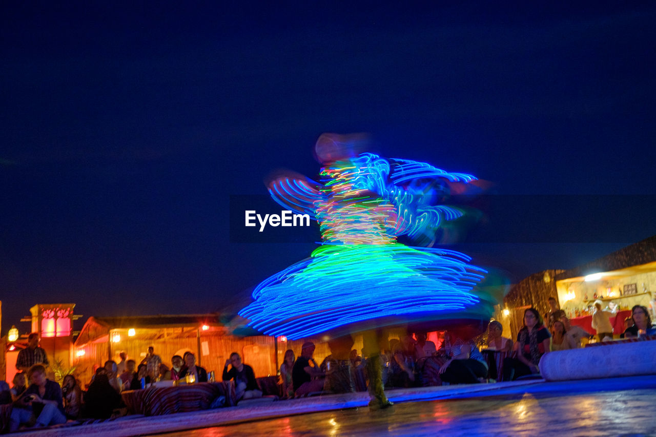 night, illuminated, large group of people, blue, leisure activity, outdoors, blurred motion, built structure, nightlife, arts culture and entertainment, crowd, real people, building exterior, architecture, women, sky, men, clear sky, carousel, people