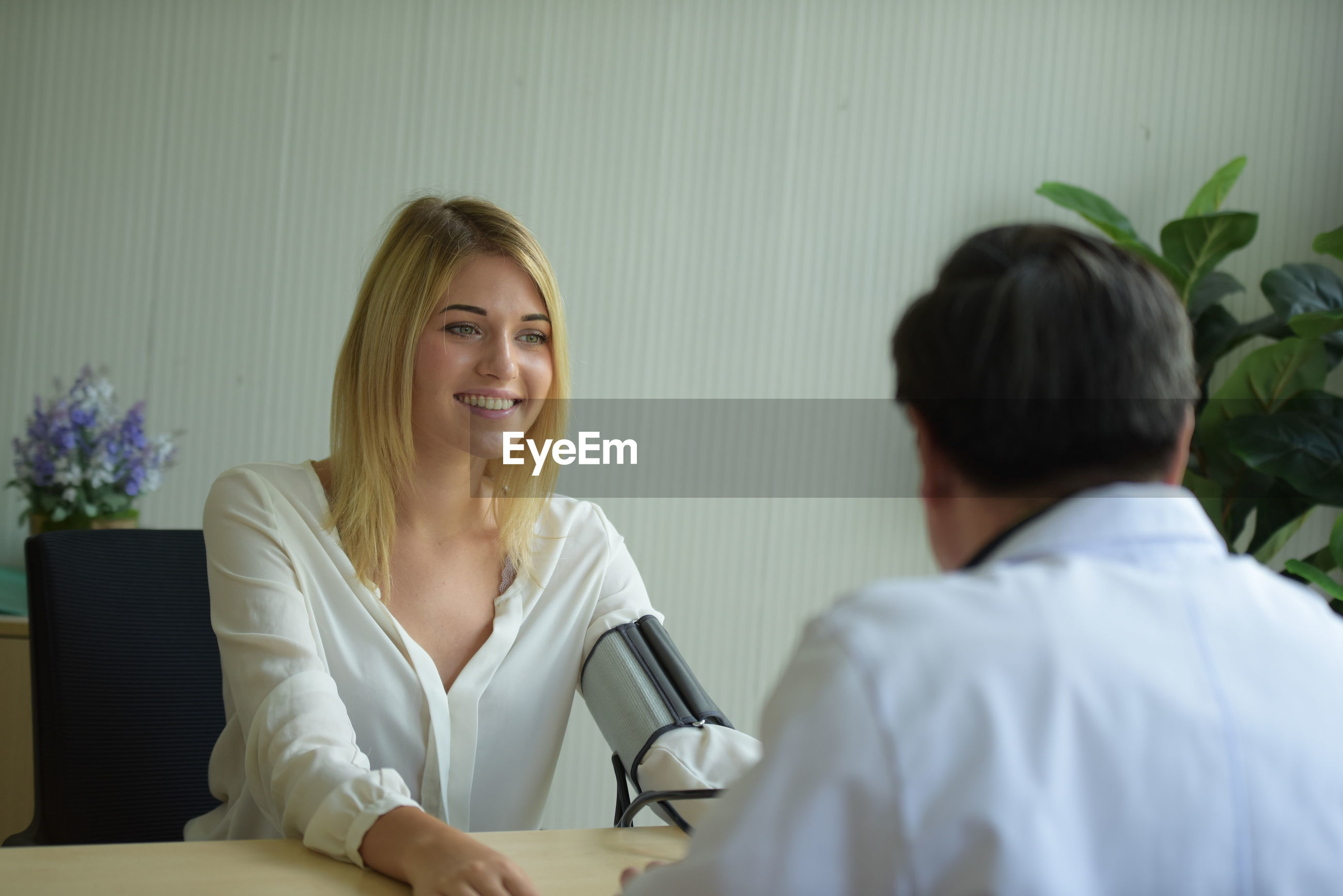 Female patient talking to doctor at clinic