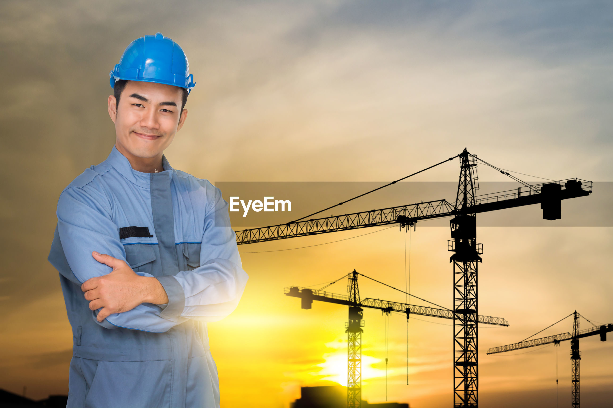 Portrait of man wearing hardhat while standing at construction site